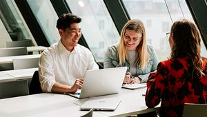Drei Studierende vor einem Laptop sitzend