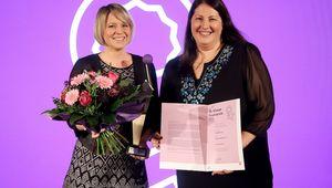 Martina Mara hält einen Blumenstrauß und die Preisstatue in der Hand, Kathrin Gaal eine Urkunde, beide lächeln in die Kamera.