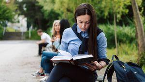 Studierende auf Parkbänken sitzend