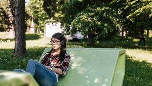 Studierende, die auf Enzo im Park sitzt und Musik hört