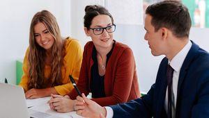 Zwei Studentinnen und ein Studenten sitzen an einem Tisch und sprechen miteinander