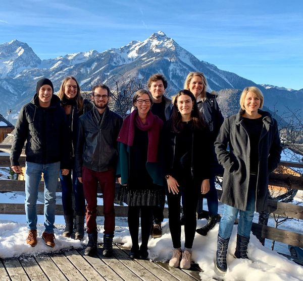 The 8 members of the Robopsychology Lab team standing in the snow and sun in front of the mountains of Vorderstoder