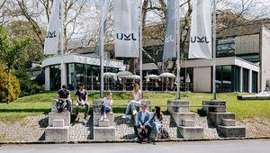 Studierende, die auf den Stiegen vor den Fahnenmasten sitzen