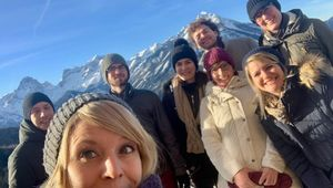 All 8 members of the Robopsychology Lab Team standing in front of the winter mountains of Vorderstoder