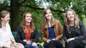 vier lachende Studentinnen auf Parkbank sitzend