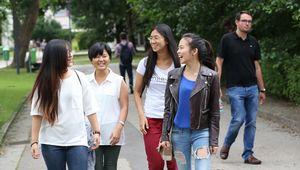 lachende Studentinnengruppe beim Gehen