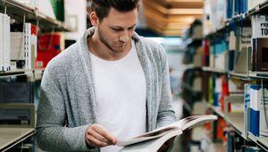 lesender Studierender zwischen zwei Bücherregalen stehend
